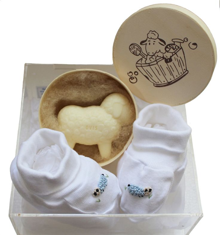 A pair of hand embroidered booties in pink, blue or beige in a smart perspex box with a gorgeous sheep soap tucked up in sheep's wool.
