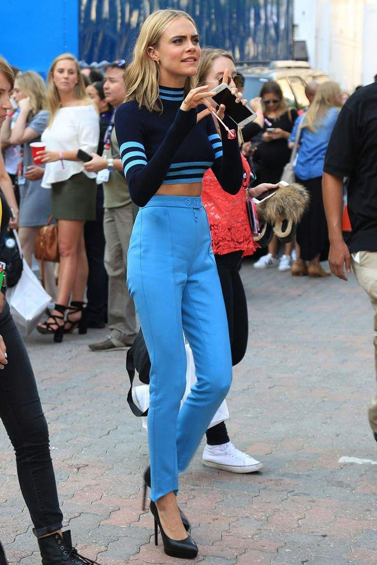 Cara Delevingne : jersey cropped en azul marino con rayas en azul claro y pantalones de tiro alto a juego, ambos de Versace; y salones negros con plataformas.