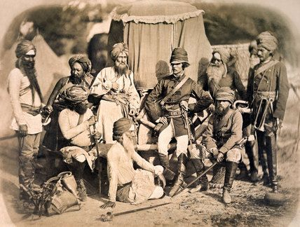 Photo shows Hodson's Horse, a body of loyal Indian horsemen formed during the Mutiny of 1857 by Lt William Hodson. Their distinctive uniforms included scarlet turbans and shoulder sashes over beige tunics. This photograph taken shortly after the final capture of Lucknow in Mar 1858. Hodson was killed during the assault.The identity of the two British officers, seems most likely to be Lt Clifford H Mecham and Asst Surgeon Tom Anderson (sitting). Anderson was with him when he died on 11 Mar…