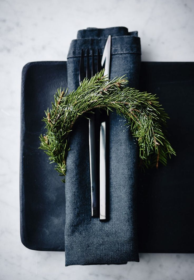 Pretty Christmas napkin decoration with a spruce branch at the table.