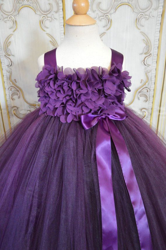 The sugar plum dress is such a popular dress, the materials used to make it sell out fast, get yours today! This flower girl tutu dress is made with chiffon hydrangea flowers over the front of a crotchet tutu top, with a plum tulle skirt and tied with plum straps and bows. A beautiful and stunning dress. Perfect for a wedding, or any formal event! The chiffon hydrangeas now come in more colors, convo me with your request. white, ivory, black, grey, champagne, brown, lavender, purple, plum…