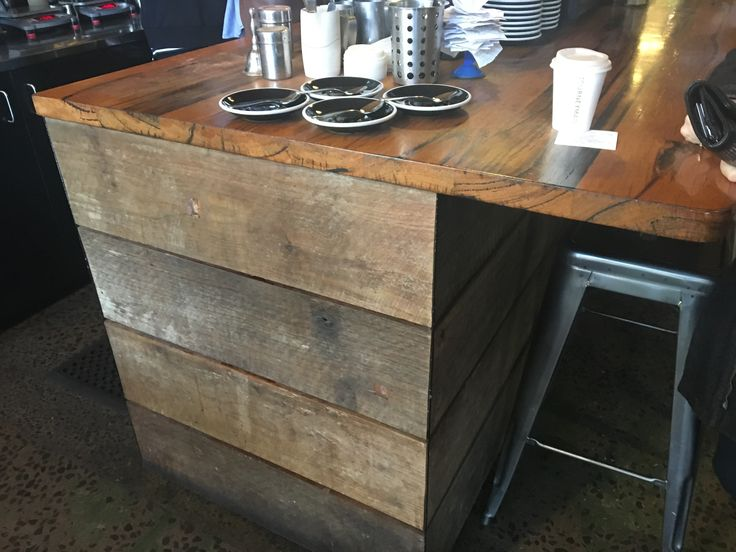 This timber bench uses an unfinished natural timber and a varnish finished counter top to create a contrast in materials. The finish on the counter top also is protective so that it can withstand ware and tare of the tasks carried out on this surface.