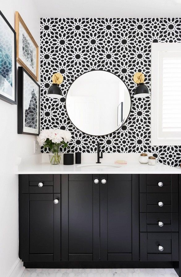 Black and white pattern wallpaper in  bathroom with round mirror, gold and black sconce lighting, and black vanity.