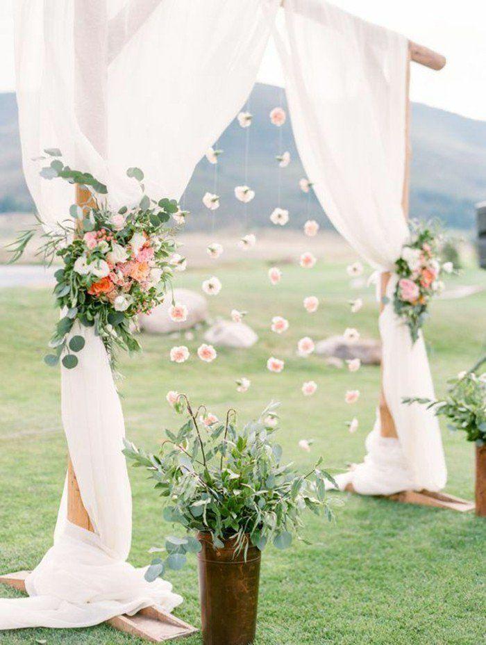 une arche mariage réalisée avec du voilage et et des bouquets de feuillages et fleurs