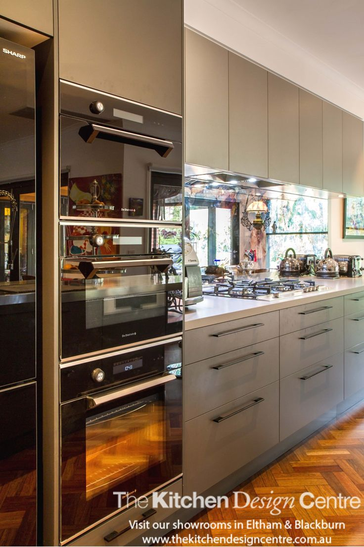 A moody kitchen designed as the perfect backdrop to a quirky couple. Dark finishes, antique mirror splashback and a curved stainless steel island benchtop make this kitchen completely unique. www.thekitchendesigncentre.com.au @thekitchen_designcentre