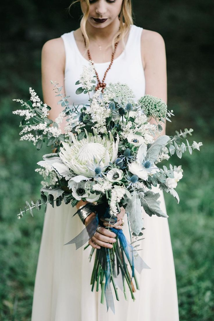White protea, eucalyptus, anemones, blue thistle, and queen anne's lace make up with striking bridal bouquet #Cedarwoodweddings ndigo Design Inspiration by Cedarwood Weddings | Cedarwood Weddings