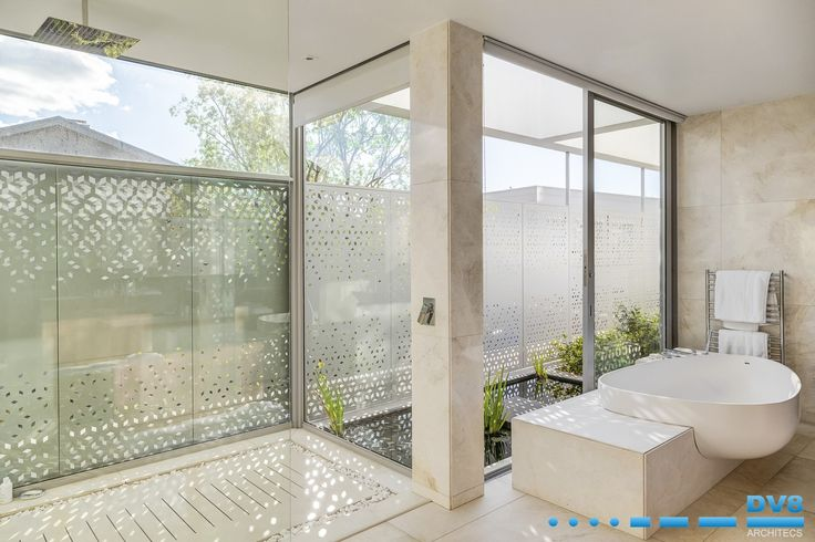 Modern Japanese house. Bathroom with screens creating interplay of light and shadow. Water feature and planting integrating internal and external space. Wabi Sabi.