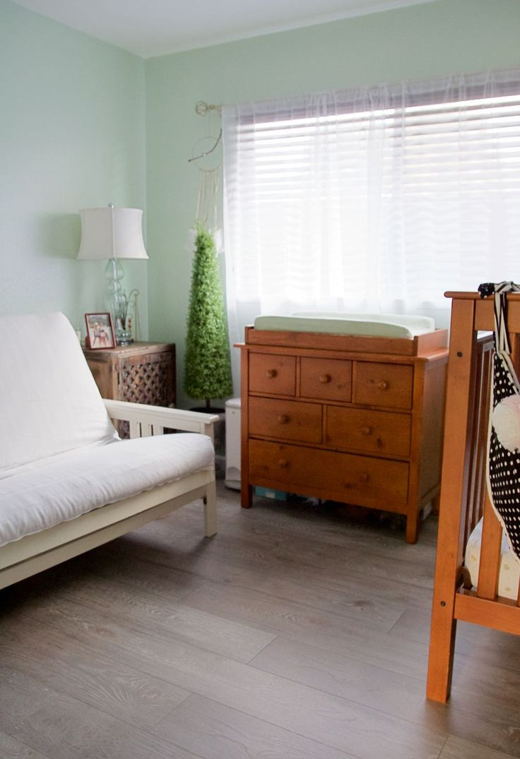 mint green nursery with white futon