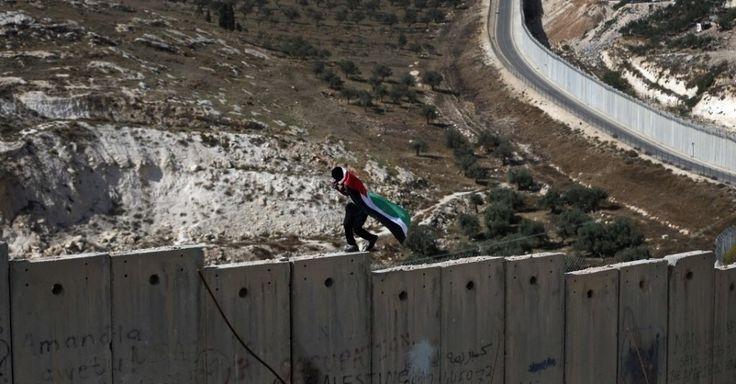 Homem coberto com a bandeira palestina anda sobre o polêmico muro construído pelo governo israelense que separa a cidade de Abu Dis, na Cisjordânia, da parte leste de Jerusalém, em Israel. A região vive confrontos que já deixou dezenas de palestinos e israelenses mortos