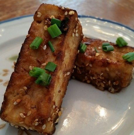 Have you ever tried the golden sesame tofu from Whole Foods? Yum. Here is a copycat recipe that may even be better.  The secret here is the cornstarch, it gives the tofu its chewy coating, but you have to sprinkle it over the tofu evenly and with a light hand; otherwise itll get gloppy(using a wire mesh works well). Youll find toasted sesame oil and mirin(or you can sub rice wine vinegar) in the Asian sections of well-stocked supermarkets.  Adapted from Dianacooks. Thanks Diana!