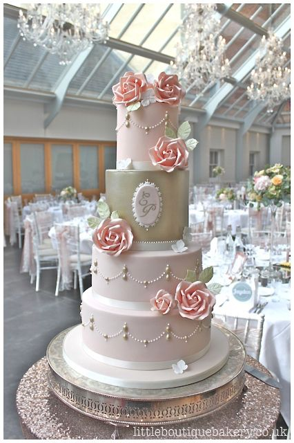 Blush sugar roses on pale pink icing and gold lustre detail wedding cake with pearl swags and monogram of wedding couples initials. Set up in the light filled atrium at Botley's Mansion, Surrey.