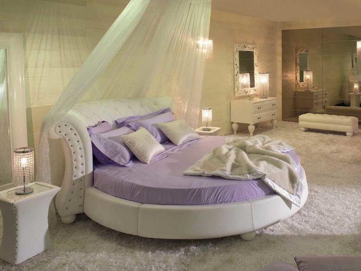 Приятный светло-сиреневый отлично смотрится в этой просторной комнате в теплых светлых тонах на фото 1. Стоящая под стенкой круглая кровать, балдахин для большей романтичности и уединения, мягкое светлое напольное покрытие, комод с зеркалом, пуфик и тумба с такими же изгибами, фигурными ножками и плавными линиями – интерьер современной спальни подобран очень тщательно.  Прочитать статью http://flaterra.ru/spalnya/mebel-s/kruglaya-krovat-vybor-dizain-foto-ceni.html полностью.