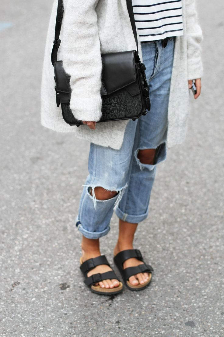 Mija is wearing a grey mohair cardigan from Acne Studios, ripped boyfriend  jeans from Citizens of Humanity, bag from Alexander Wang, striped tee from  NoName ...