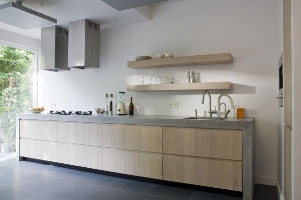 Moderne keuken met betonnen keukenblad. Door het robuuste betonnen aanrechtblad krijgt deze moderne houten keuken een stoer uiterlijk. Het keukenblad loopt aan de zijkanten door tot op de grond. Er is in deze keuken veel bergruimte ontstaan door de diepe en brede lades. Hierdoor hoeven er geen bovenkastjes geplaatst te worden, maar volstaan een paar dikke planken. De twee vierkante afzuigkappen maken het plaatje helemaal af!