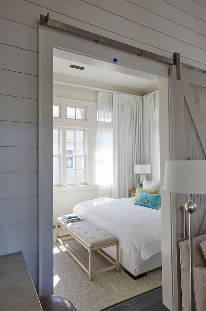 Sliding barn door. Small Bedroom with Pecky Cypress Barn Door on Rails. A pecky cypress barn door on rails opens to a beach style bedroom filled with an off white upholstered bed dressed in green and blue velvet pillows as well as a gray French bench placed at the foot of the bed. sliding-barn-door Geoff Chick & Associates