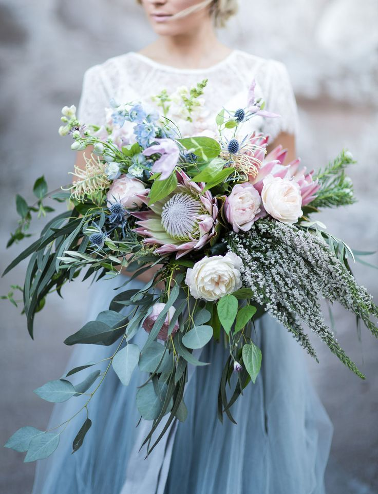 A blue hued protea bouquet with soft pink pops and lots of greenery.