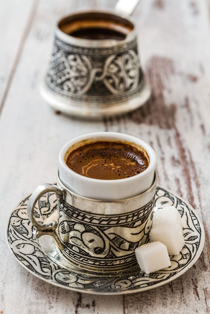 Turkish coffee in a traditional silver demitasse cup and matching pot.