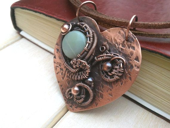 This is a copper pendant made with a faceted amazonite stone. I cut and textured this piece by hand and the design has been wire wrapped onto the