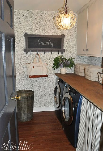 A fun little chalkboard sign with hooks like this one from @homegoods along with the hamper and a basket for each family member helps with organization in this laundry room that underwent an inexpensive makeover to help make it more functional. (sponsored pin)