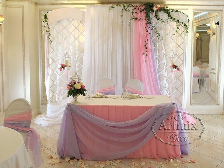 Беседка, украшенная тканью и декорированная плющом и живыми цветами.