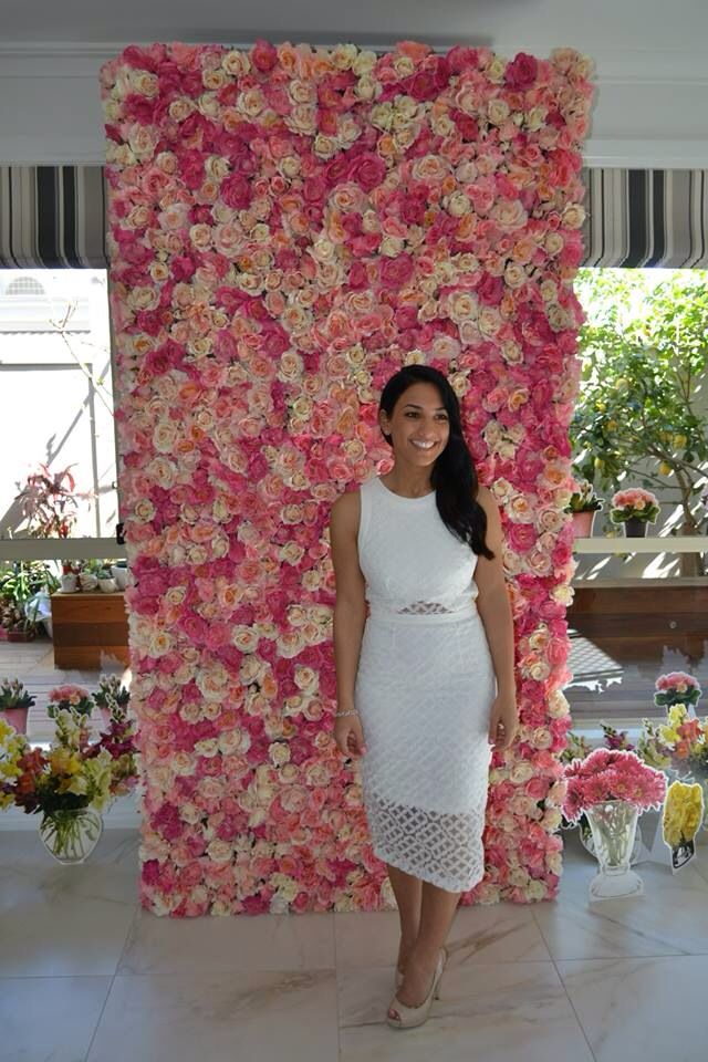 Stunning Maria at her kitchen tea standing in front of the bed of roses wall #whiteluxe #flowerwall #melbourne