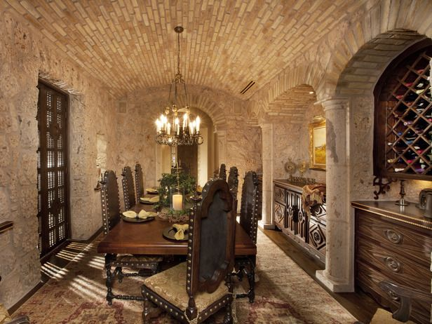 Italian Renaissance appeal with a comfortable and cozy dining experience. Cantera stone walls, often used in Spanish and Southwestern designs, immediately set this room apart from the home's plastered walls and intricate murals. The brick barrel-vaulted ceiling subtly mimics the kitchen's ceiling detail, while providing a delicate contrast from the stone walls.