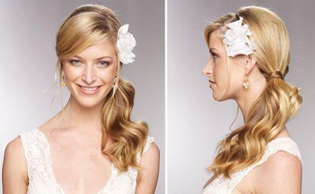 Low Side Ponytail With Flower - Curl the ends of your hair into loose waves. Pull into a low side ponytail and wrap a section of hair around the ponytail to hide the elastic. Secure a flower pin behind one ear for a fresh look