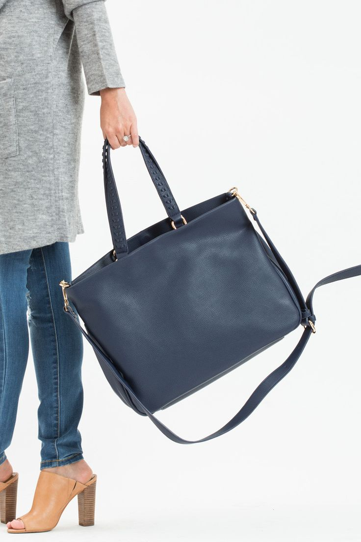 Tired of your every day black handbag? Add some variety to your closet with our new navy purse! We love the perfect Fall color and handles that tuck in for versatile wear! This handbag has three inner