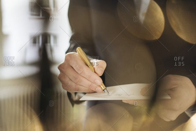Hand of businessman writing with golden fountain pen on notepad