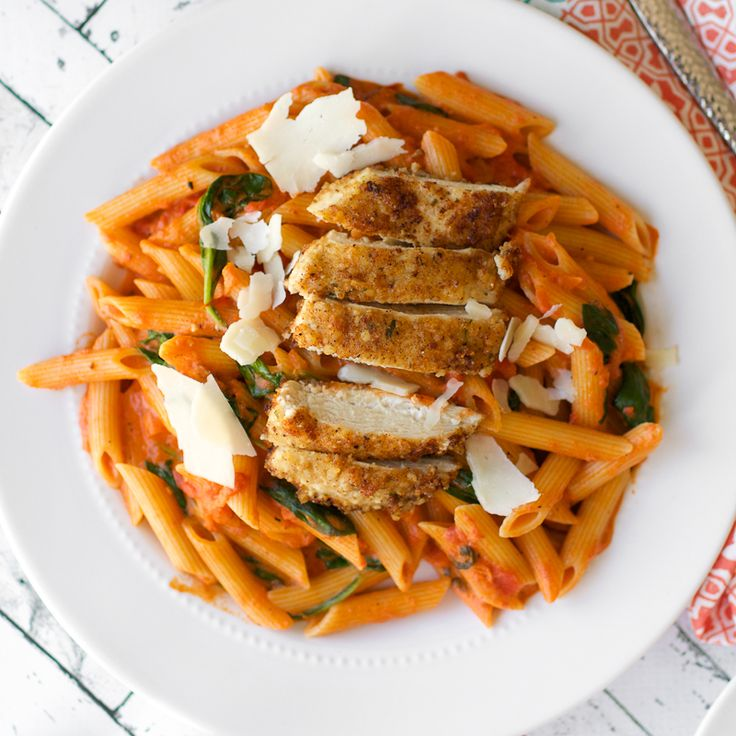 Copy cat recipe of Noodle's and Co Penne Rosa. A spicy tomato cream sauce tossed with penne, tomatoes, and spinach - topped with parmesan chicken.