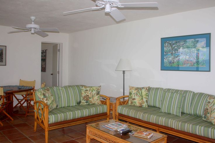 The comfortable living room with Saltillo tiles, Caribbean artwork, large wicker sofa with matching loveseat and coffee table beckons the guests to relax.  The entrance into the master bedroom is just beyond the living room.