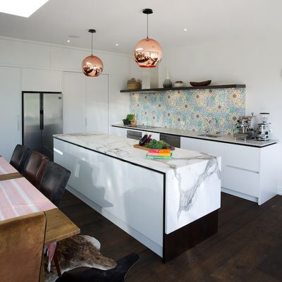 This kitchen has some standout features including an Arebescato Marble waterfall benchtop, copper lights and colourful Moroccan inspired tiles. Designed by Hayley Dryland