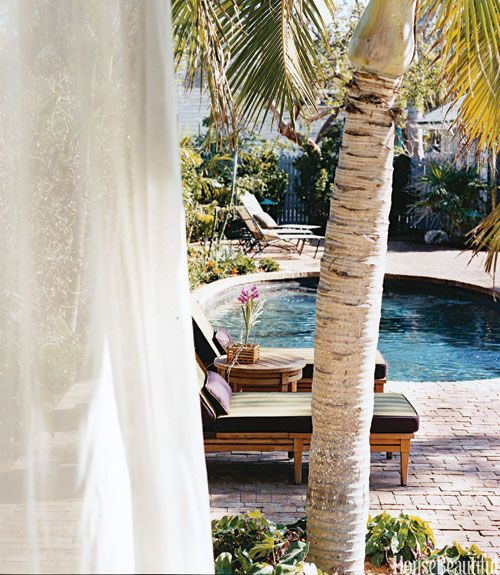 From the outdoor sitting and dining room in designer Malcolm James Kutner's house in Florida's Key West, you can see the pool through gaps in the sheer curtains. Poolside chairs from McGuire in Perennials' Big Stripe fabric. Sun loungers are Brown Jordan, with Peter Fasano Key Biscayne cushions.   - HouseBeautiful.com