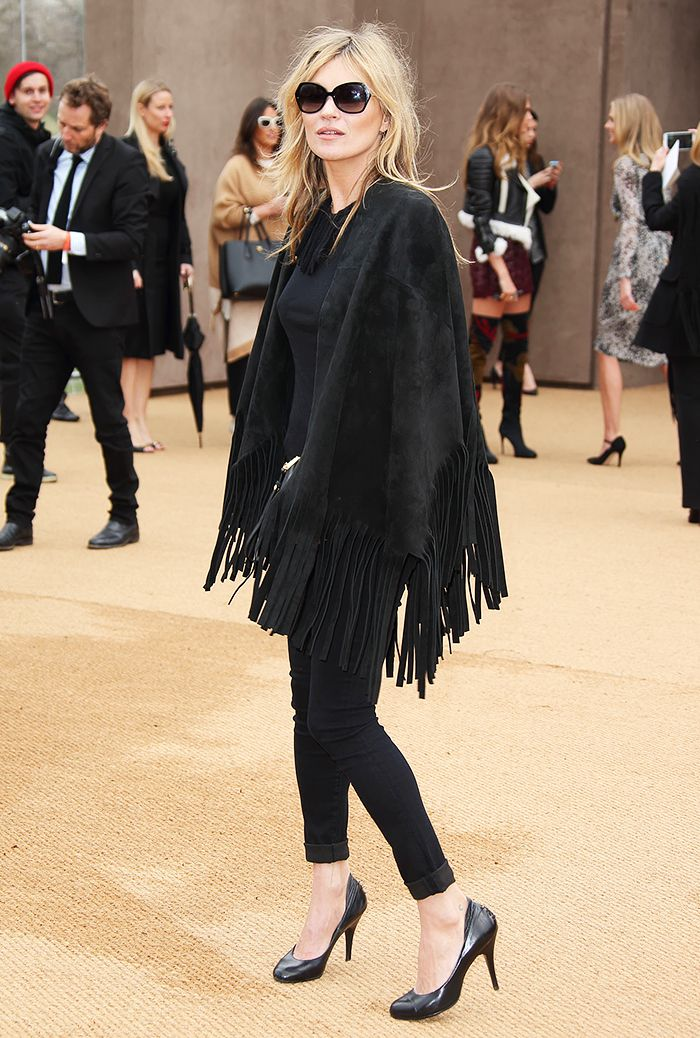 Kate Moss wearing a black cape with fringe, black cuffed jeans, and black pumps: