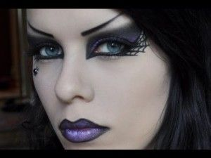 Halloween makeup idea for witches with a pale foundation and dark eye makeup and dark purple lip makeup.
