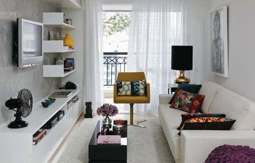 Na sala de estar, predomina o branco da estante de laca (Marcenaria Medeiros) e do sofá (Dpot). Pontos de cor surgem na poltrona (Fernando J...