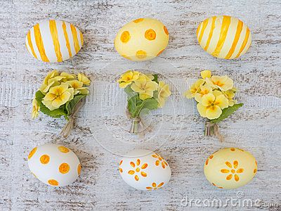 Easter eggs painted by stripes, dots and flowers and primrose bouquets on the white wooden board