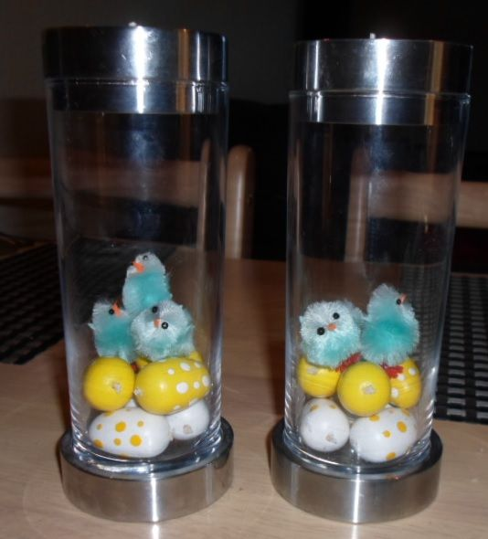 Candlesticks decorated with white and yellow easter eggs and blue easter chickens.