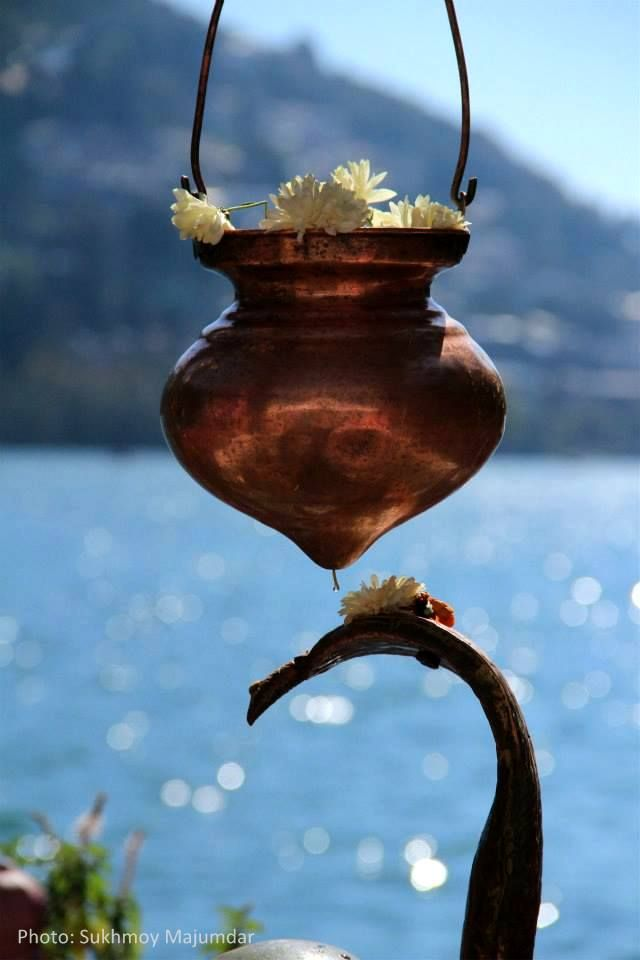 The copper urn is filled with milk and drips continuously onto the snake and Shiv Ling. Temple in Nainital, Uttarakhand.