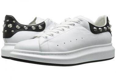 These sneakers are the <strong>Alexander McQueen Studded Sneakers</strong>. They're available in white and black. They are laced sneakers and they have metal studs on the back of them on the heel. They're leather lined sneakers with a lightly padded