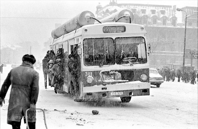 """ROMANIA, University Square, Bucharest, 12.1984.Bus with empty gas cylinders - """"Comrade"""" Elena Ceausescu had requested the use of LPG, to save fuel. But the tanks on the buses were always empty, because LPG did not yet exist..© Andrei Pandele / EST&OST"""