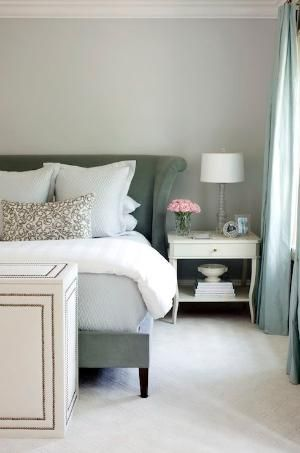 Sophisticated bedroom design with gray walls paint color, gray velvet Hickory Montauk bed, white traditional nightstand, light blue matelasse & shams, turquoise blue silk curtains window panels and white nailhead trim storage box. by rochelle
