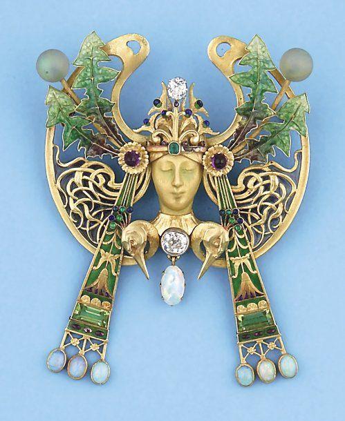 ART NOUVEAU - Broche - pendentif en or jaune, émail et émail plique à jour représentant une tête de femme ornée de diamants, d'émeraudes, d'opales, d'améthystes et péridots. Travail de Paul Briançon - Ancien chef d'atelier de R. LALIQUE. Vers 1900. (Petit éclat à l'émail). P. 45,2g.  <3