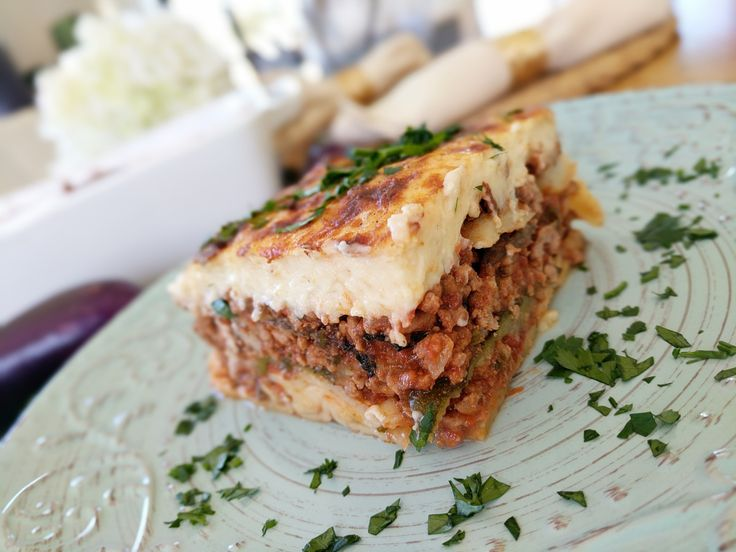 Moussaka  A delicious variation of the traditional moussaka. The Eggplant and zucchini layers alternate with a smooth herbed tomato and mince sauce and finally topped with a creamy ricotta bechamel sauce. Th…