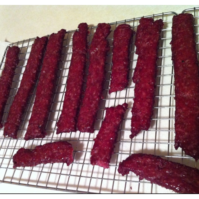 GROUND VENISON JERKY 5 lb. ground venison 1 1/2 tsp. Morton's Tender Quick salt 9 tsp. table salt 2 tsp. each pepper and garlic powder 1/2 tsp. cayenne pepper 1 1/2 tsp. cardamom 1 tsp. Accent seasoning msg 1 oz. liquid smoke and 1 oz. water Mix ground venison with spices. Roll meat between sheets of waxed paper into 1/4 inch thickness. Mix liquid smoke and water; brush on meat. Bake at lowest degree of heat on your oven control for 3 to 4 hrs,When dry cut in strips & store