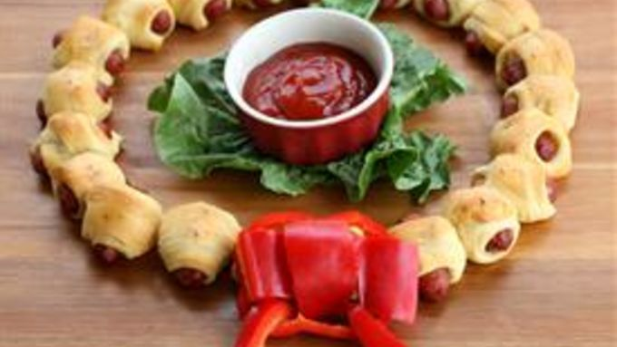 Create a festive and edible appetizer wreath with mini sausages wrapped in crescent dough and brushed with a seasoned glaze.