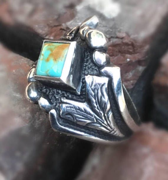 "The Rockin Out ""Turquoise Jade"" Sterling Silver Engraved Ring has a unique border with an 6mm bezel set princess cut Kingman Turquoise stone mounted in the middle of the ring and engraved scrolls on the side of the band. This ring comes in half sizes 4 through 12. All of the turquoise will vary in color from piece to piece. This ring can be purchased on our Etsy store for $89."