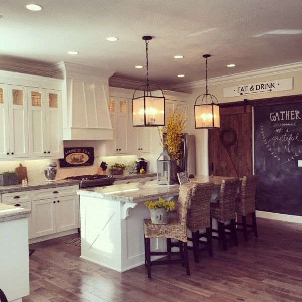 Love this white kitchen with lots of farmhouse flair including the rolling barn wood door, chalkboard wall and double lanterns over the large island - part of the Eclectic Home Tour of Yellow Prairie Interiors kellyelko.com