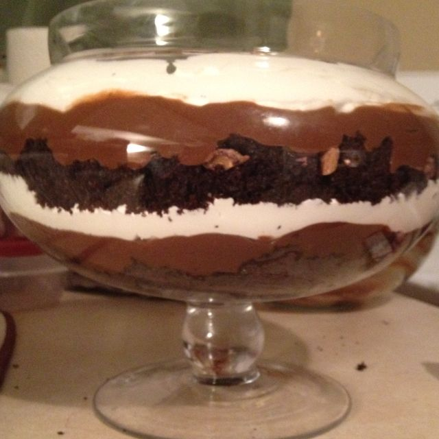 Chocolate cake, pudding, cool whip and crushed Heath bars layered in a pretty bowl.