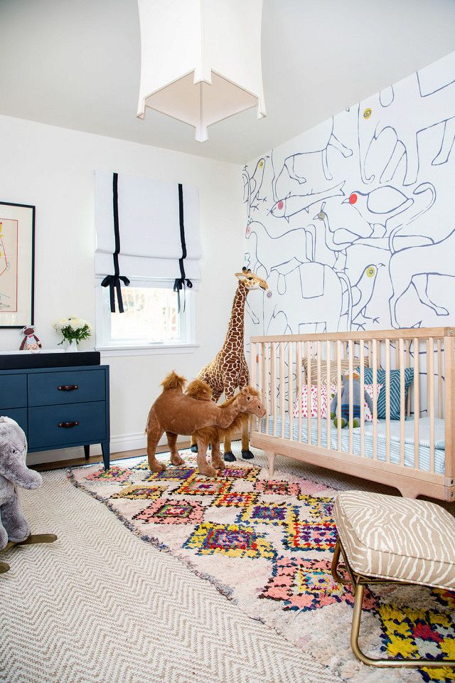 Children's nursery with a lantern, printed wallpaper, a simple wood crib, layered rugs, and large plush toys